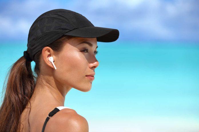 Frau mit Kopfhörer und Kappe am Meer
